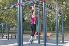 Entrenamientos caucásicos jovenes de la mujer en la tierra de deportes del parque Levantando en la barra vertical, ropa de deport foto de archivo libre de regalías