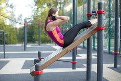 Entrenamientos caucásicos jovenes de la mujer en la tierra de deportes del parque La muchacha hace el excersise abdominal, en neg fotos de archivo