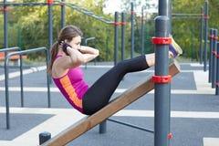 Entrenamientos caucásicos jovenes de la mujer en la tierra de deportes del parque La muchacha hace el excersise abdominal, en neg foto de archivo