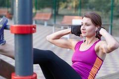 Entrenamientos caucásicos jovenes de la mujer en la tierra de deportes del parque La muchacha hace el excersise abdominal, en neg imagen de archivo