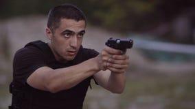 Entrenan a los guardias de seguridad para tirar los armas en la radio de tiro almacen de metraje de vídeo