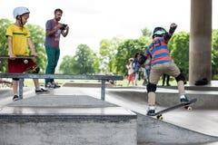 Entrenan a los individuos jovenes divertidos potentes en un parque del patín Fotos de archivo