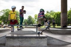 Entrenan a los individuos jovenes divertidos potentes en un parque del patín Imágenes de archivo libres de regalías