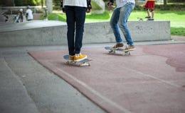 Entrenan a los individuos jovenes divertidos potentes en un parque del patín Imagen de archivo libre de regalías