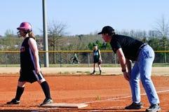 Entrenar el beísbol con pelota blanda de la muchacha Imágenes de archivo libres de regalías