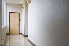 Entrence to Exit. An empty hallway leading to a closed door. Windows let light into the hall coming from the left Royalty Free Stock Images