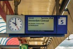 Entrene al tablero del horario y mírelo en la plataforma de la estación de tren de Weesp Foto de archivo