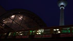 Entrene a dejar la estación de Alexanderplatz en la noche por la torre de la televisión, Berlín, Alemania almacen de video