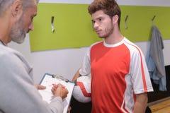 Entrene el consejo del futbolista en vestuario antes de partido Imágenes de archivo libres de regalías