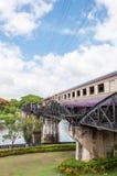 Entrene en el puente sobre el río Kwai en la provincia de Kanchanaburi, Tailandia El puente es famoso Foto de archivo
