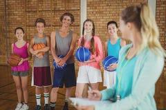 Entrene hablar con los niños de la High School secundaria en cancha de básquet Fotografía de archivo libre de regalías