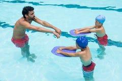 Entrene la ayuda los niños en la natación en piscina fotos de archivo libres de regalías