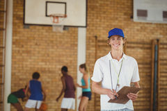 Entrene la sonrisa en la cámara mientras que equipo de la High School secundaria que juega a baloncesto en fondo Fotografía de archivo libre de regalías