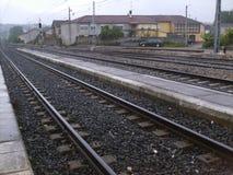 Entrene a las vías y a la vieja estación en ciudad al norte de España Fotos de archivo