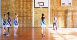 Entrene a los niños de la High School secundaria de la tutoría en la cancha de básquet 4k almacen de metraje de vídeo