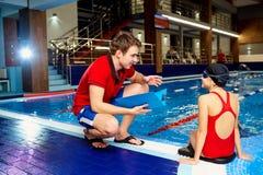 Entrene, más tranier a la muchacha del nadador en la piscina que discute con athlet Foto de archivo libre de regalías