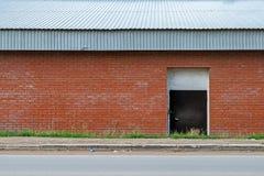 Entrepôt de façade près de la route Mur de briques avec une porte et un toit galvanisé en métal Front View Images libres de droits