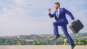 Entreprenör i målmedvetet uttryck för rörelse Bär den formella dräkten för affärsmannen portföljhimmelbakgrund Affärsman arkivfoton