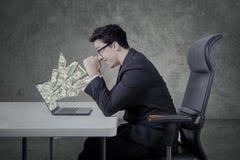 Entreprenör med pengar från bärbara datorn Arkivbild