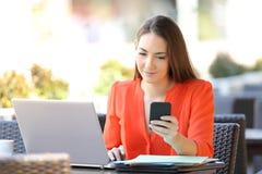 Entrepren?r som kontrollerar telefonen som arbetar i en coffee shop arkivfoto