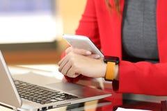 Entreprenör som synkroniserar den smarta klockan och telefonen arkivbilder