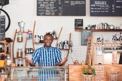 Entrepreneur africain amical se tenant derrière le compteur de son café photographie stock libre de droits