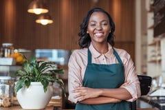Entrepreneur africain de sourire se tenant au compteur de son café photos libres de droits