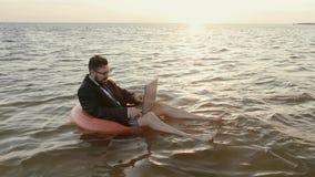 Entrepreneur au milieu de la mer sur un cercle gonflable d'enfants fonctionnant avec un ordinateur portable banque de vidéos