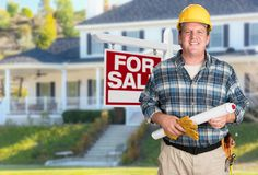 Entrepreneur avec des plans et casque antichoc devant pour le signe d'objet immobilier de vente photographie stock