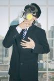 Entrepreneur avec le masque de gaz dans le bureau images stock