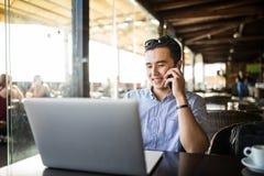 Entrepreneur bel travaillant au client de consultation d'ordinateur portable à côté du téléphone en café Travaillent en indépenda photos libres de droits