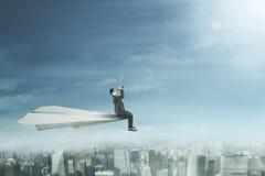 Entrepreneur with binoculars on paper plane Stock Photo