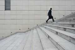 Late to work. Entrepreneur with briefcase running up the stairs as he is late Stock Photos