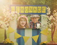 Entrepreneur Business Kids Selling Lemonade at Stand. Two little kids are selling lemonade at a homemade lemonade stand on a sunny day with a sign for an royalty free stock images
