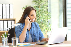 Entrepreneur calling on phone working with laptop Stock Photography