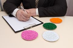The entrepreneur concludes a contract for the supply of plastic granules for industry. Plastic raw materials in granules. Polymer, plastic resin. The dye in stock photos