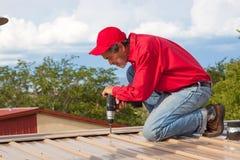 Entrepreneur, constructeur installant le toit de panneau en métal avec le masque jaune photos libres de droits