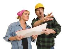 Entrepreneur dans le casque antichoc discutant des plans avec la femme sur le blanc Photo stock