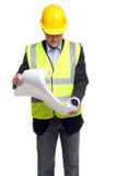 Entrepreneur de construction dans des trains de sécurité avec des plans Photos stock