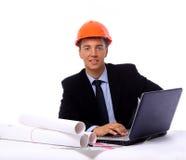 Entrepreneur de construction dans le bureau sur son lapto photographie stock