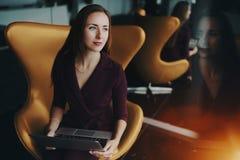 Entrepreneur de femme dans le costume pourpre avec l'ordinateur portable Images stock