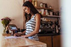 Entrepreneur de femme se tenant au compteur de facturation de son café image stock