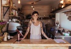 Entrepreneur de femme se tenant au compteur de facturation de son café photographie stock