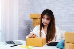Entrepreneur de femmes écrivant l'adresse sur la caisse d'emballage sur le lieu de travail dans l'offce à la maison entrepreneur  photo stock