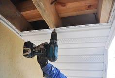 Entrepreneur de Roofer installant sur soffite et fasce de toit de maison le nouveaux Construction de toiture Soffite, installatio photo libre de droits