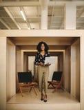 Entrepreneur de sourire de femme se tenant dans le bureau tenant l'ordinateur portable photo stock