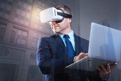 Entrepreneur de sourire utilisant le casque de VR utilisant l'ordinateur portable photo stock