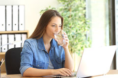 Entrepreneur drinking water and working. Entrepreneur drinking water from a glass and working on line with a laptop at office Royalty Free Stock Photography