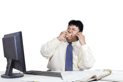 Entrepreneur eating burger while working. Asian businessman working in the office while eating burger and talking on the mobile phone Stock Photos