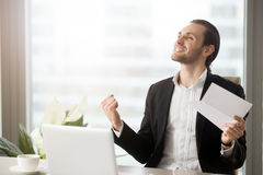 Entrepreneur excited with achievements in work. Successful businessman saying yes with document in hand. Happy excited entrepreneur celebrates victory Stock Photography